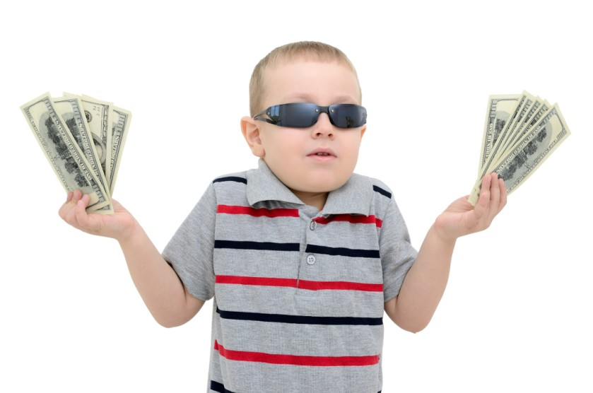 Boy in amazement holding money on white background